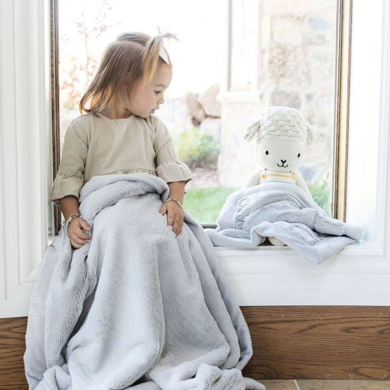 Little girl sitting in a window next to a cuddle and kind doll with a light grey blanket on their lap