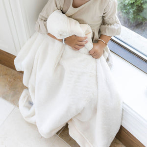 Little girl hugging ivory baby blanket in a window