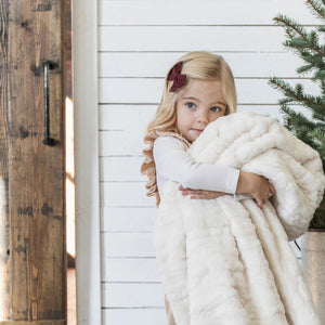 Little girl hugs super cozy ivory blanket.