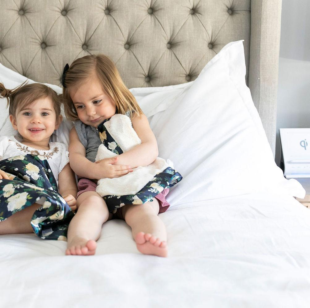 Children cuddle on the bed with their soft ivory floral mini baby bedding.