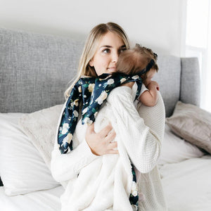Mom cuddles baby wrapped in an ivory blanket with floral backing.