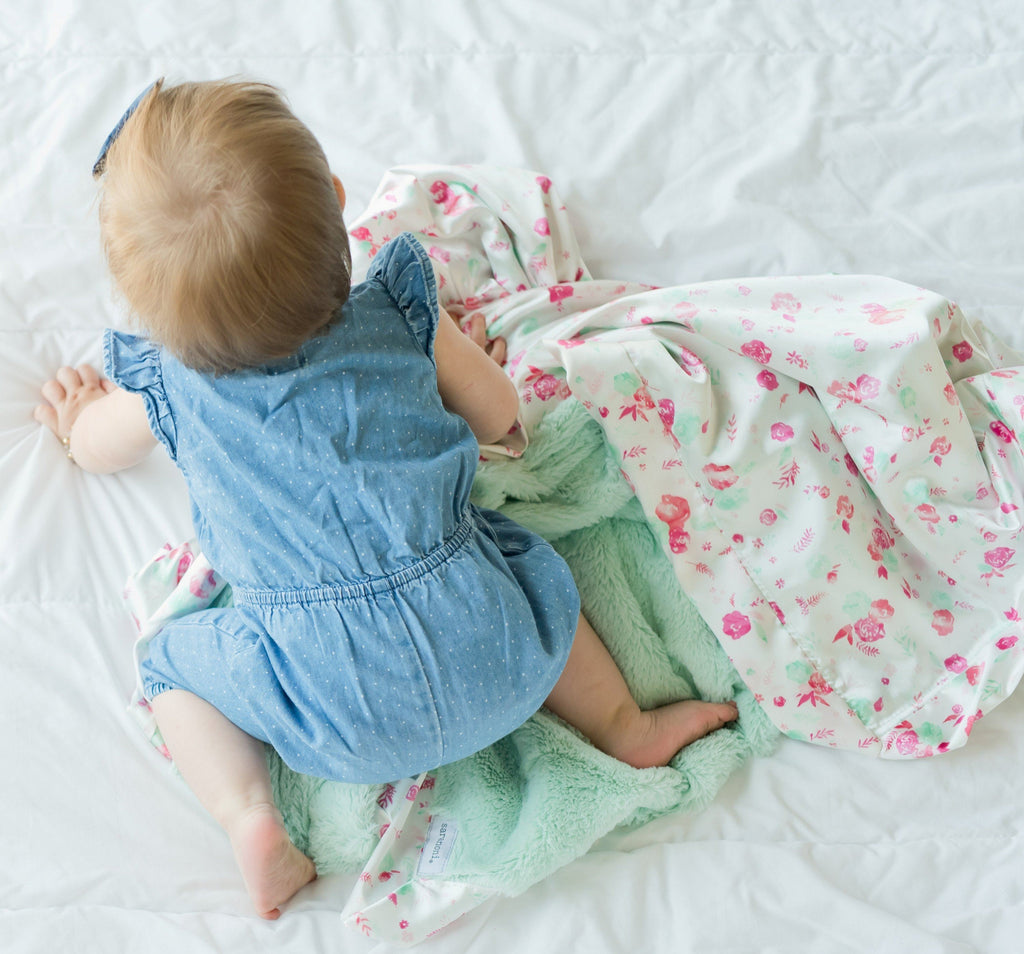 baby crawles away with her mint blanket with flowers in satin.