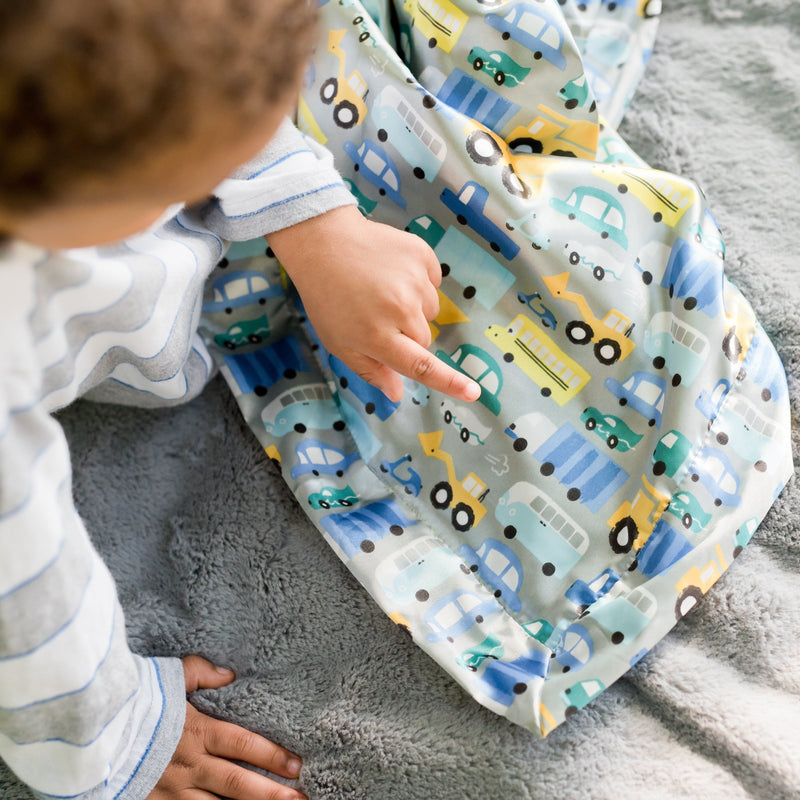 Toddler boy points to the car print on a satin baby boy blanket.