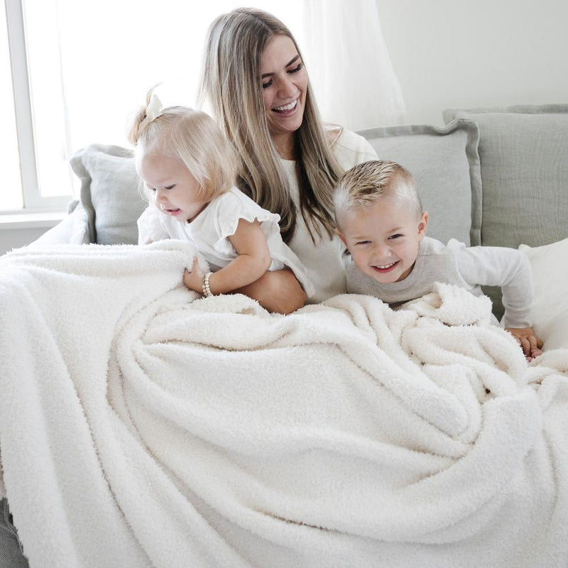 Family sits on couch under ivory oversized blanket while holding their baby girl
