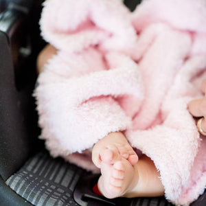 Cute infant feet covered by a stretchy, light pink mini blanket made with bamboo material.