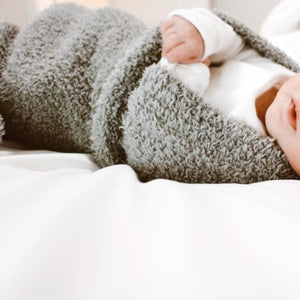 Baby swaddled in a fluffy, gray security blanket.