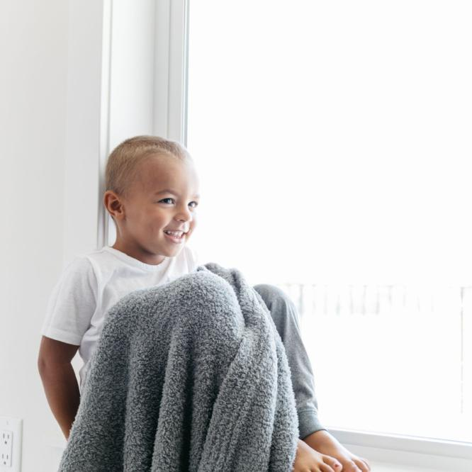 Toddler boy sitting in the window with his gray stretchy soft blanket.