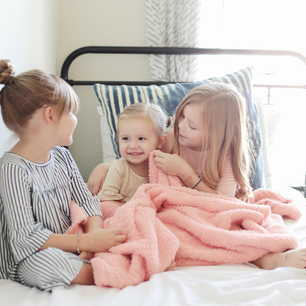Little girls play with their peach soft stretchy blanket.