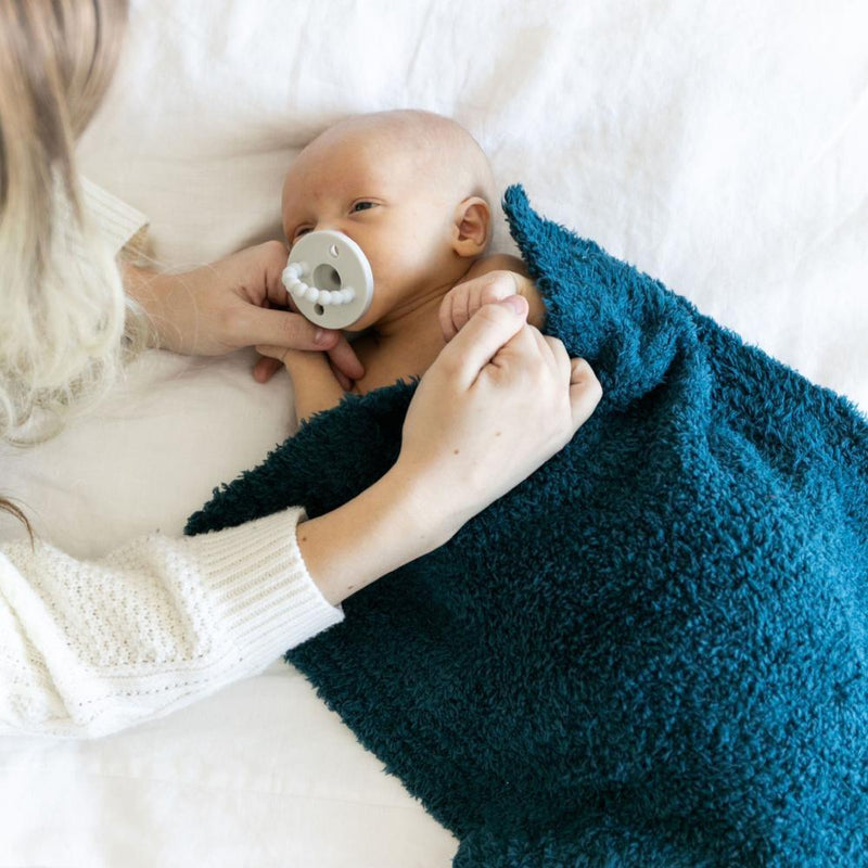 Newborn grasps mother's finger while snuggled in a deep navy Bamboni mini.