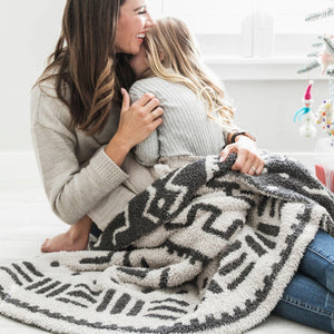 Mom and daughter wrapped in African patterned throw blanket.