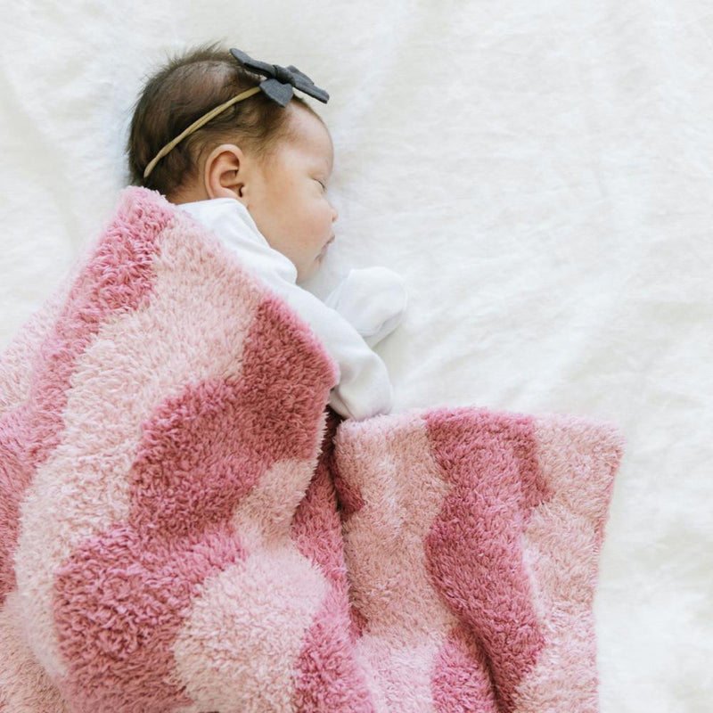 Goregous newborn girl sleeps under a dual toned pink lovey blanket with scalloped details.