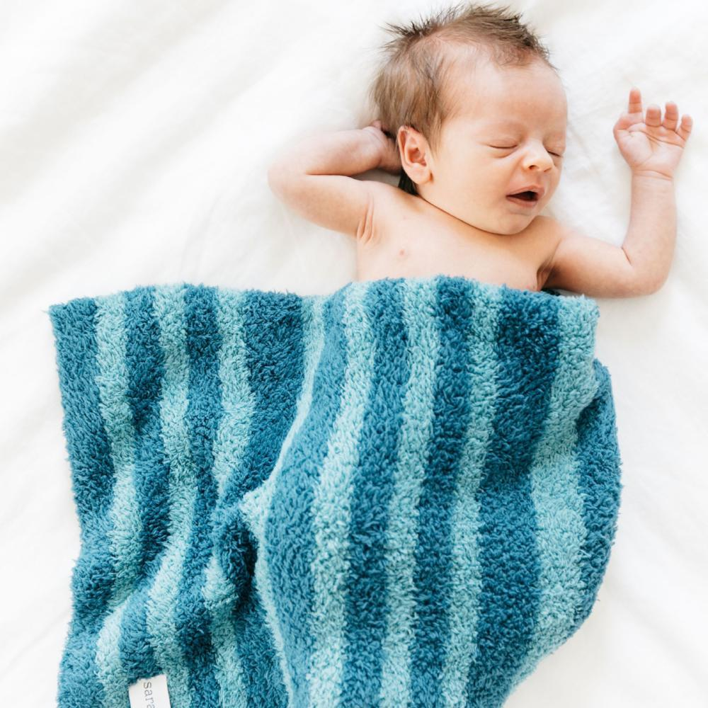 Baby boy yawning underneath a super soft double layered blue baby blanket.