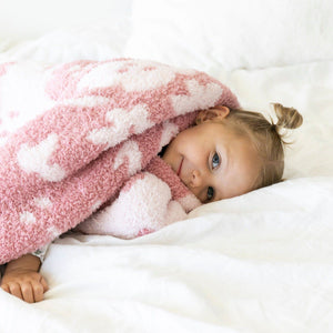 Little girls cuddles in super soft and stretchy pink floral blanket.
