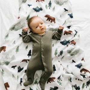 Baby boy lays on light weight muslin swaddle blanket with bears, trees, mountains, and birds.