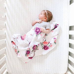 Baby laying in crib with purple floral lightweight blanket