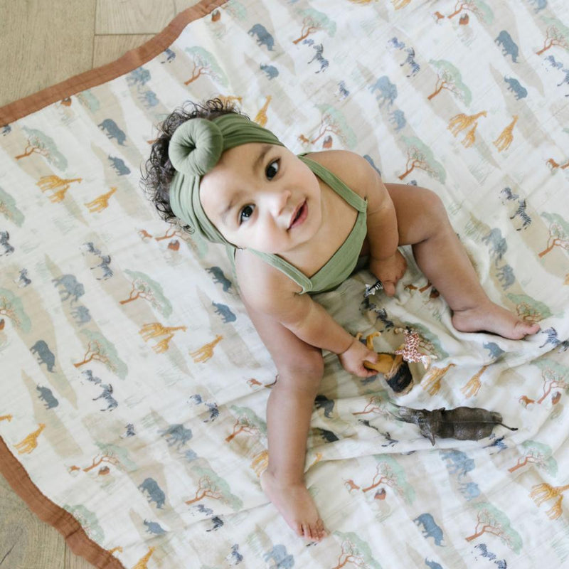 Beautiful Baby girl playing on a hand crafted amazing African Safari baby muslin quilt.