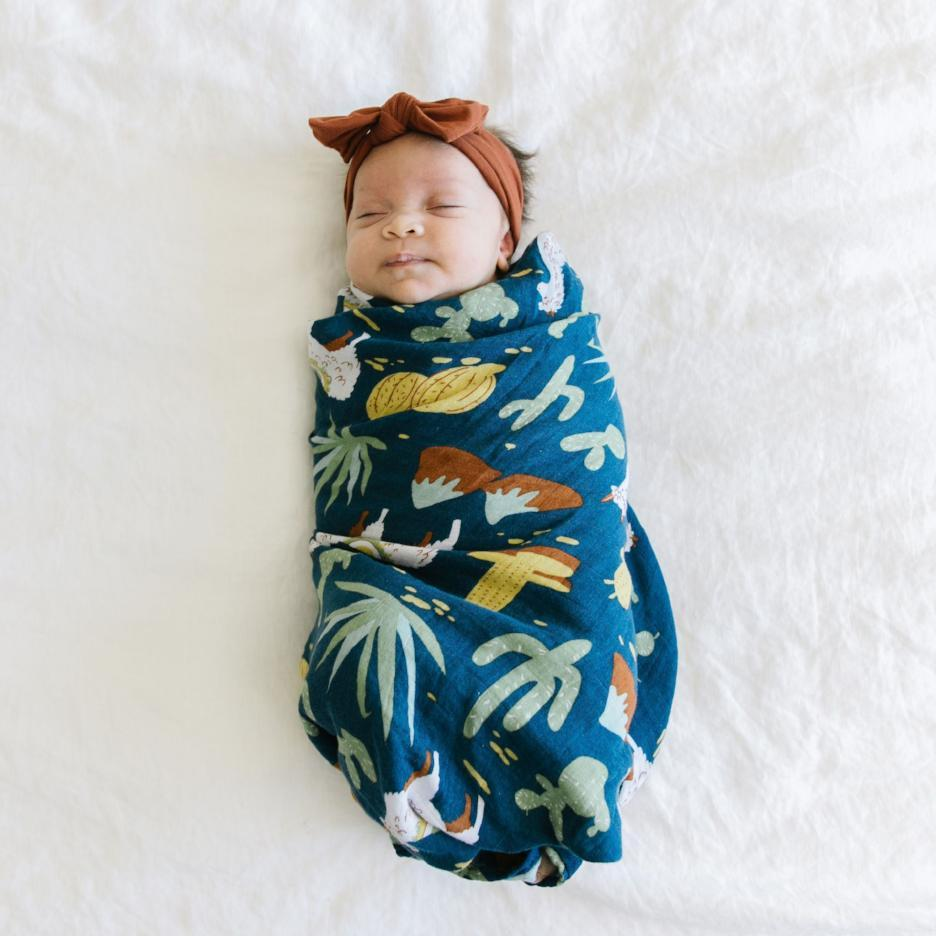 Newborn baby girl wrapped in a Cactus and Llama baby blanket swaddle.