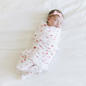 New born girl swaddled in a muslin blanket with delicate pink and red flower print.