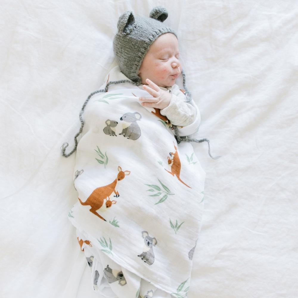 Baby sleeping in kangaroo and koala bear baby muslin swaddle.