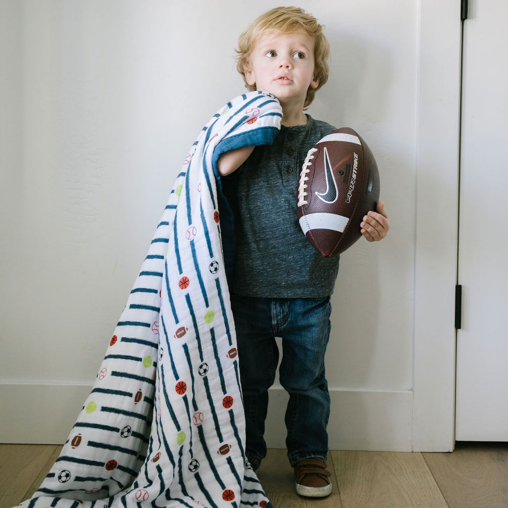 Little boy holds football in one hand and sports quilt in the other.