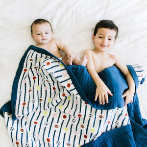 Baby and Toddler boys snuggled up in a blue basketball, football, baseball, soccer boys quilts.