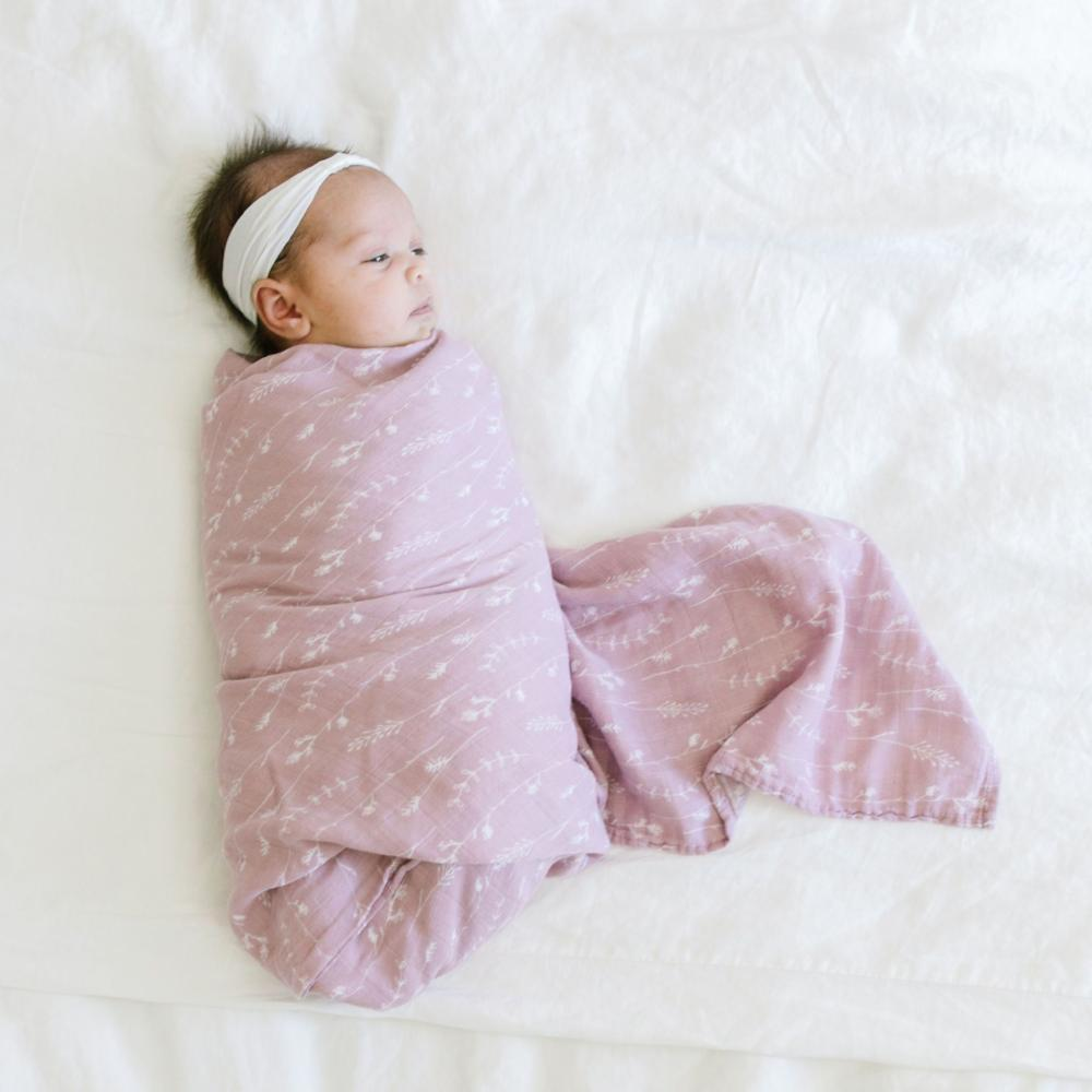 Baby girl wrapped in wildflower muslin swaddle blanket.