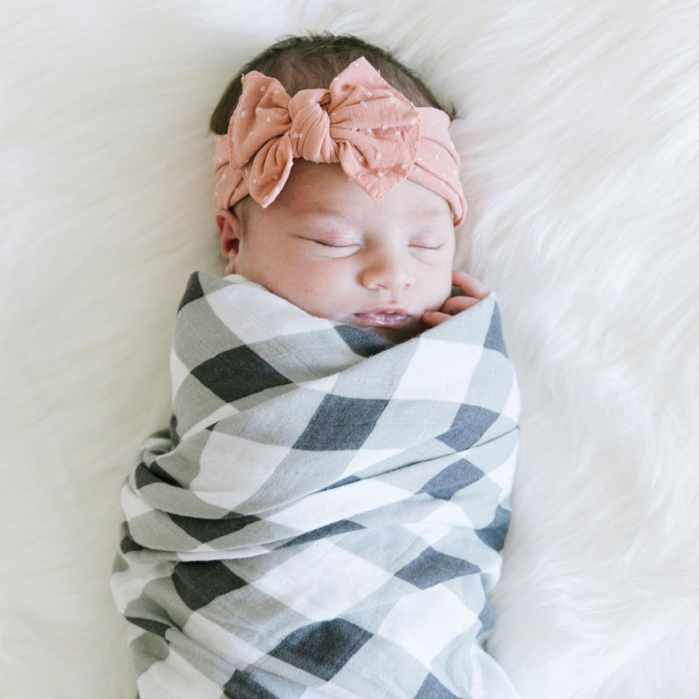 Newborn baby girl wrapped in a buffalo plaid muslin swaddle blanket laying on a bed.