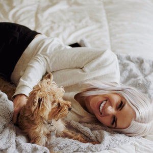 Woman playing with her puppy on a soft, comfy extra large throw blanket.