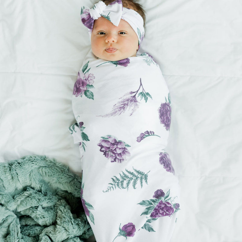 Baby swaddled in purple floral stretchy swaddle blanket with matching bow.