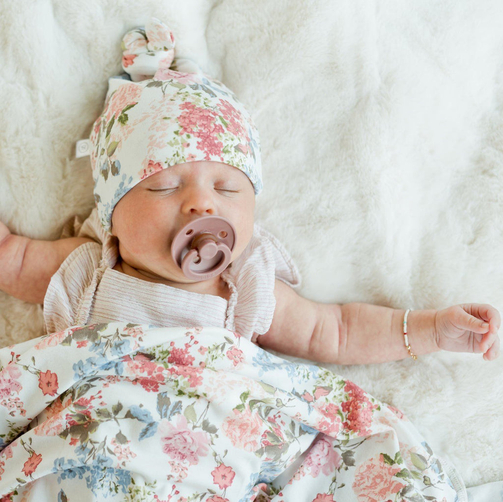 Baby sleeping under multicolored floral blanket with matching newborn hat.