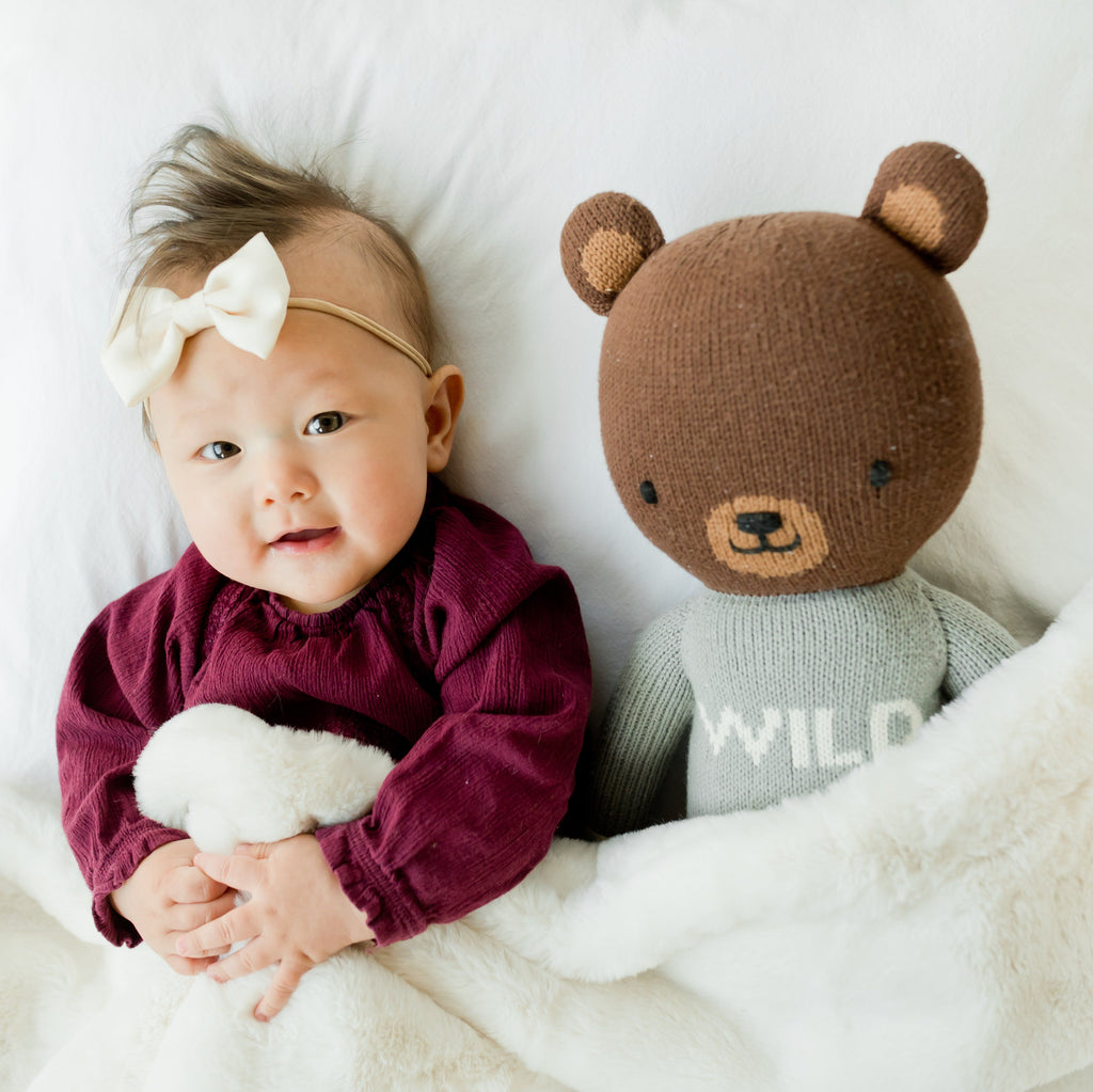 Little girl laying under plush ivory blanket with her cuddle and kind bear.