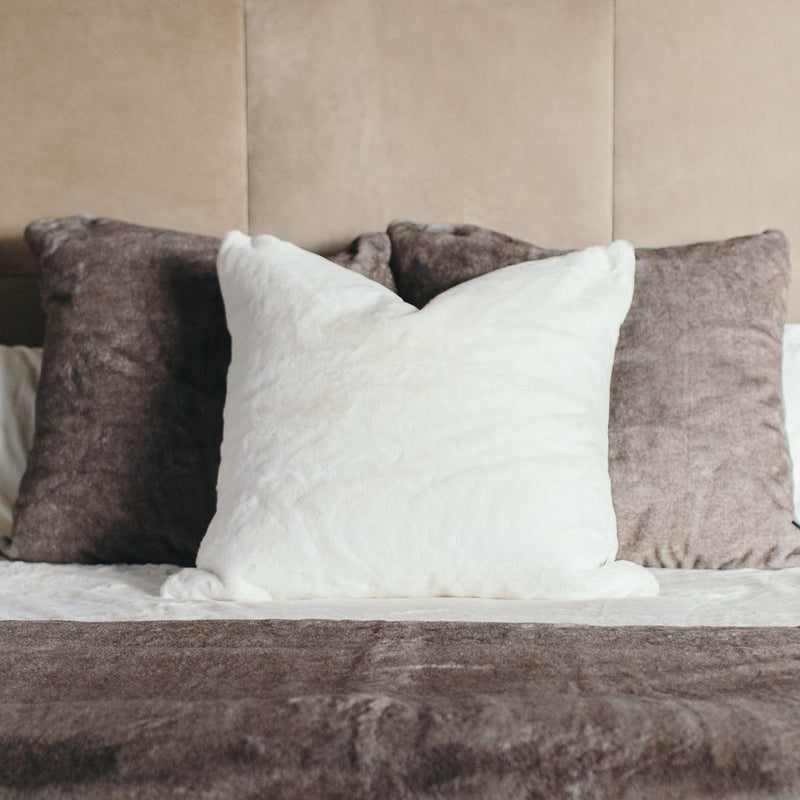 Bed with three faux fur euro pillows.