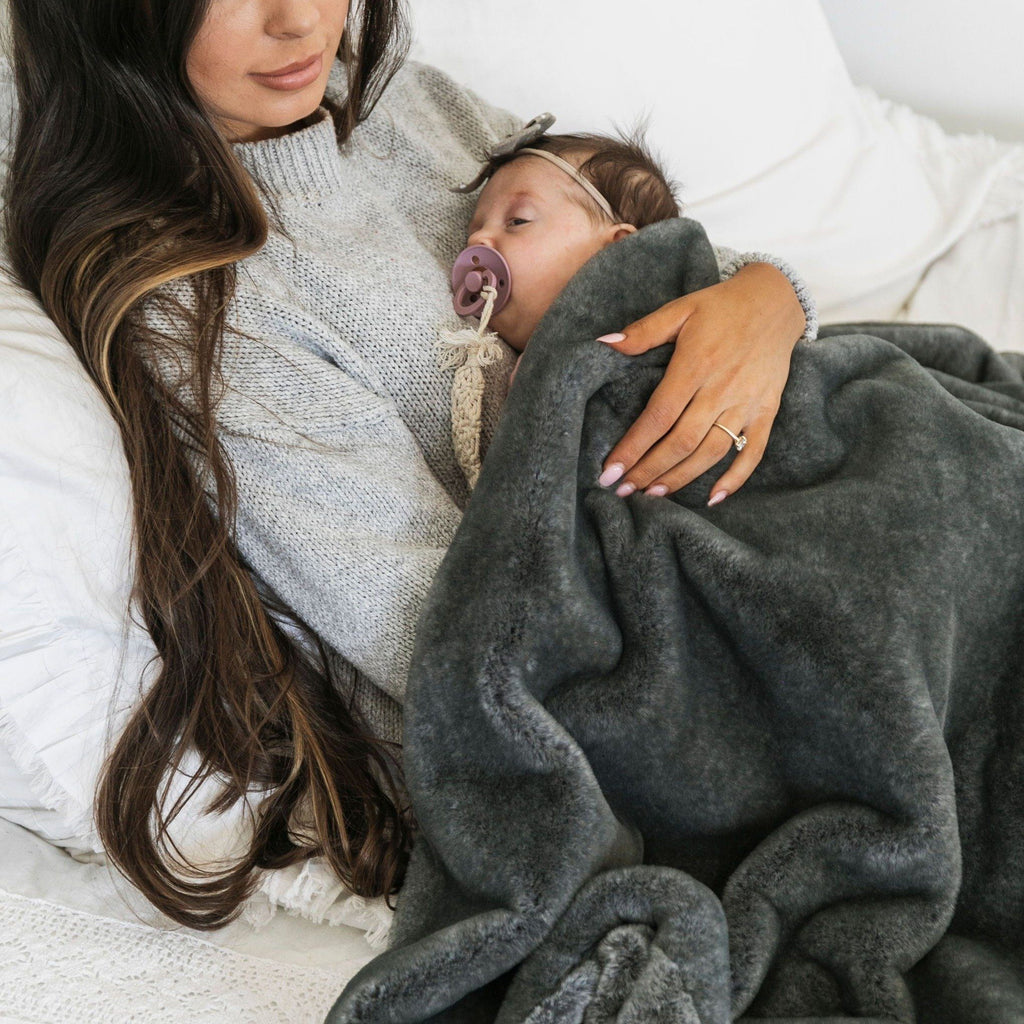 Mom holds newborn in luxurious charcoal faux fur throw blanket.