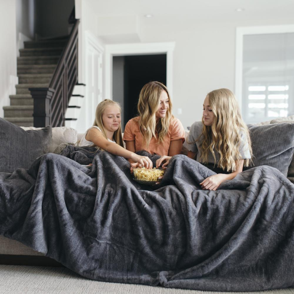 Mother and daughters snack covered in a dark, silky faux fur adult sized blanket.