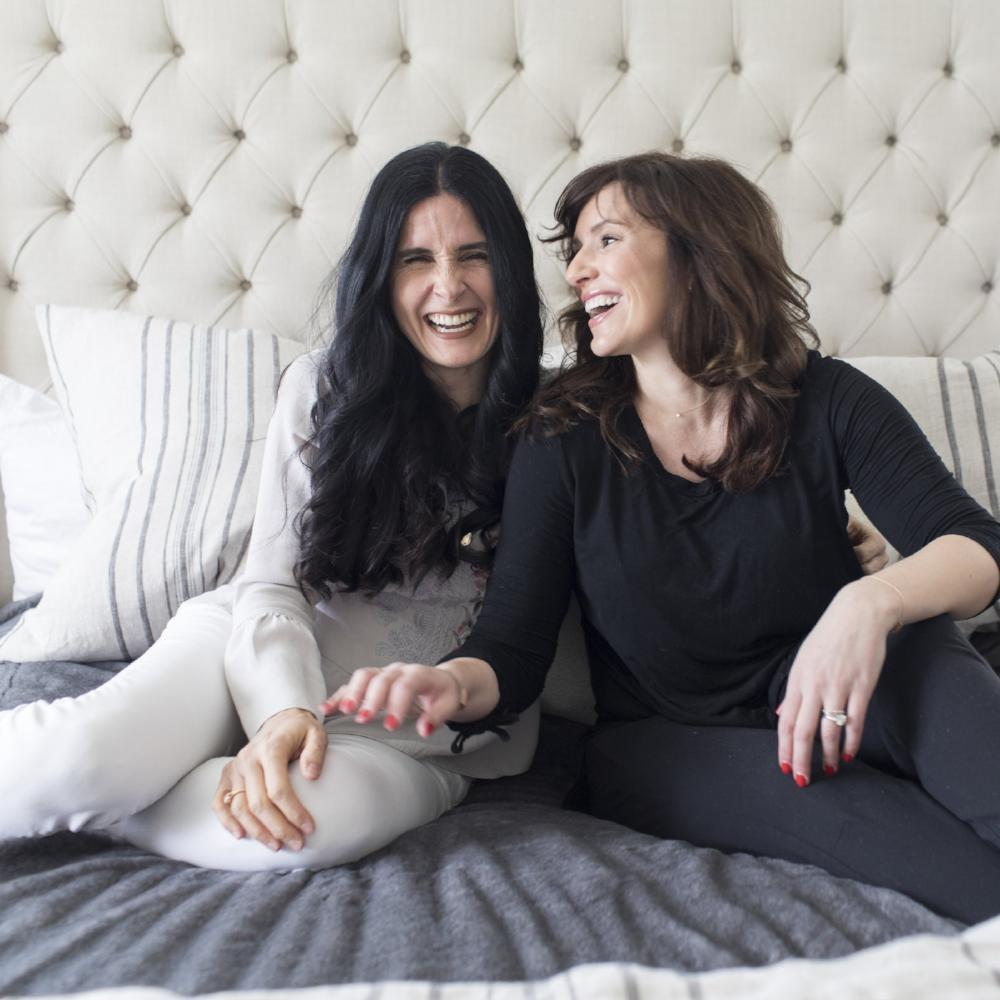 Two sister laughing while enjoying a conversation sitting on a queen bedding set.