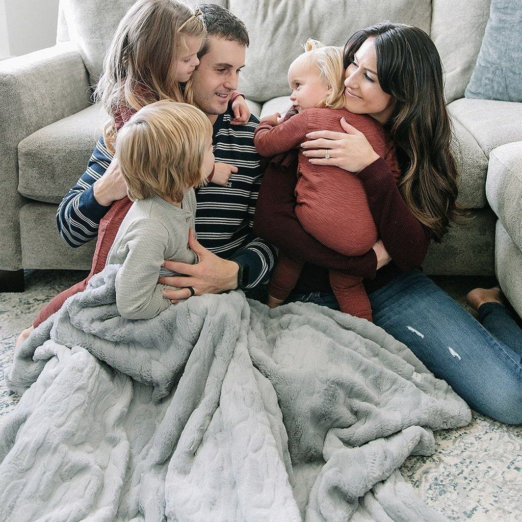 Family snuggles under soft gray throw blanket.