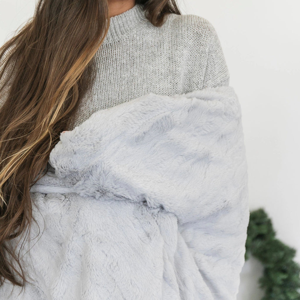 Woman wraps herself in soft silver gray faux fur blanket.
