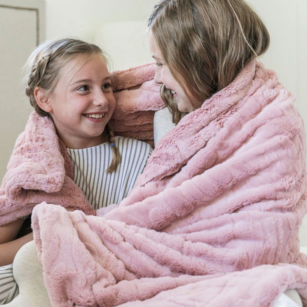 Sisters smile at each other while wrapped in blush pink throw blanket.