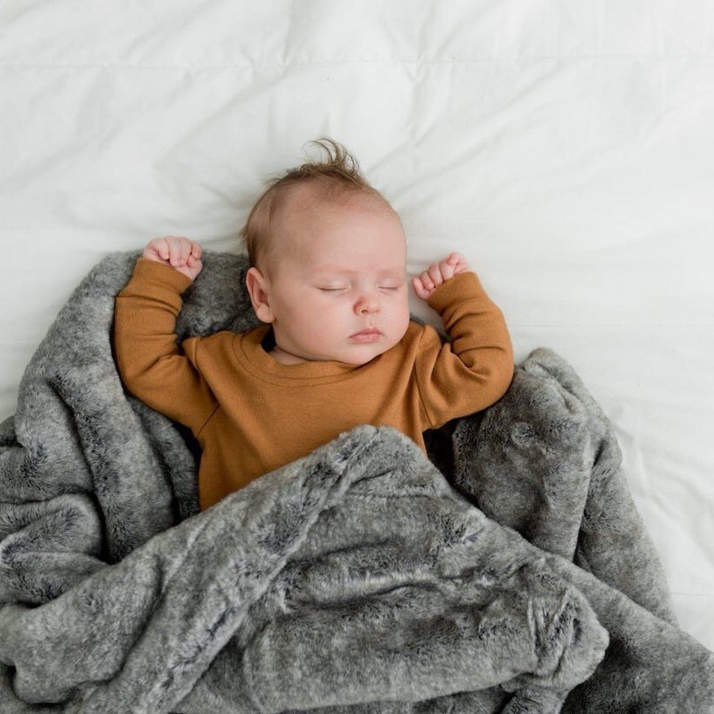 Baby sleeping with a faux fur super soft receiving baby blanket.