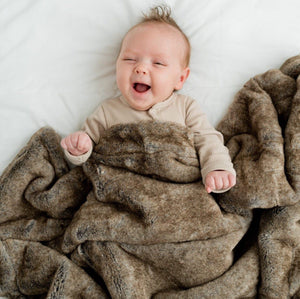 smiling baby wrapped in a beautiful brown lux baby blanket.