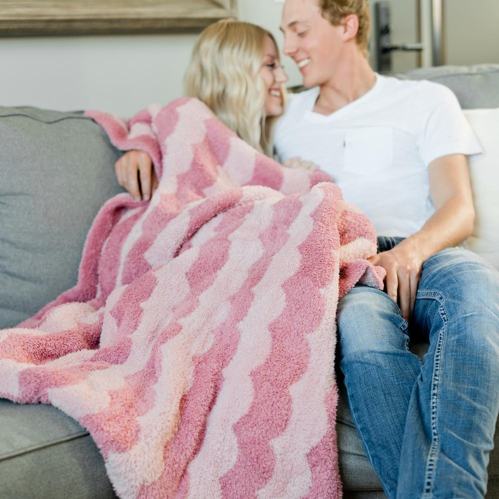 Girl wrapped up in a pink scalloped bamboni super soft throw blanket cuddled next her handsome boyfriend.