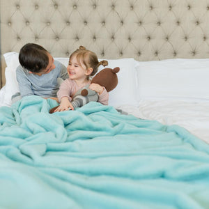 Brother and sister playfully laughing while cuddled up in an aqua blue big fluffy blanket.