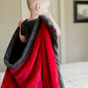 Little boy carries his comfy, vibrant red plush twin blanket.