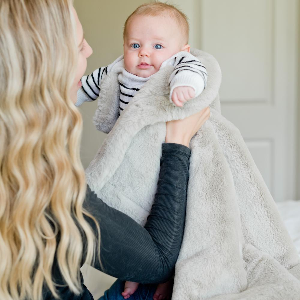 Mom holds baby in neutral taupe faux fur baby blanket.