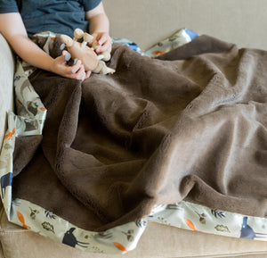 Little boy plays with animal with a brown kids blanket sits on his lap.