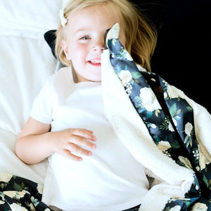Little girl cuddles ivory satin kids blanket with flowers.