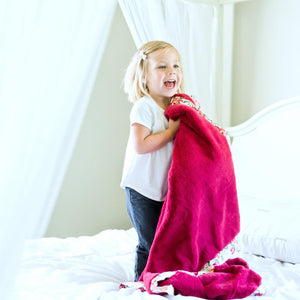 Little girl jumps on the bed while holding the softest rosy red floral blanket.