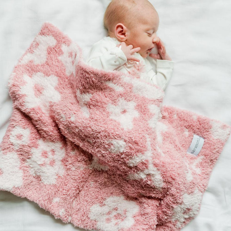 Newborn girl sleeps under a beautiful pink flower print baby blanket.