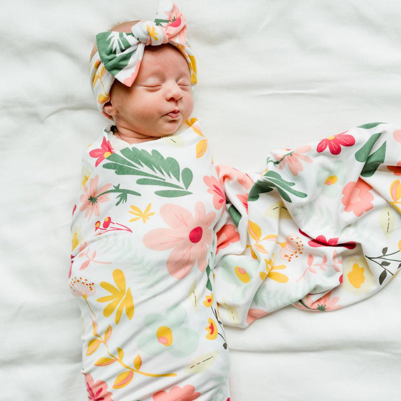 Newborn wrapped in colorful floral blanket with matching bow
