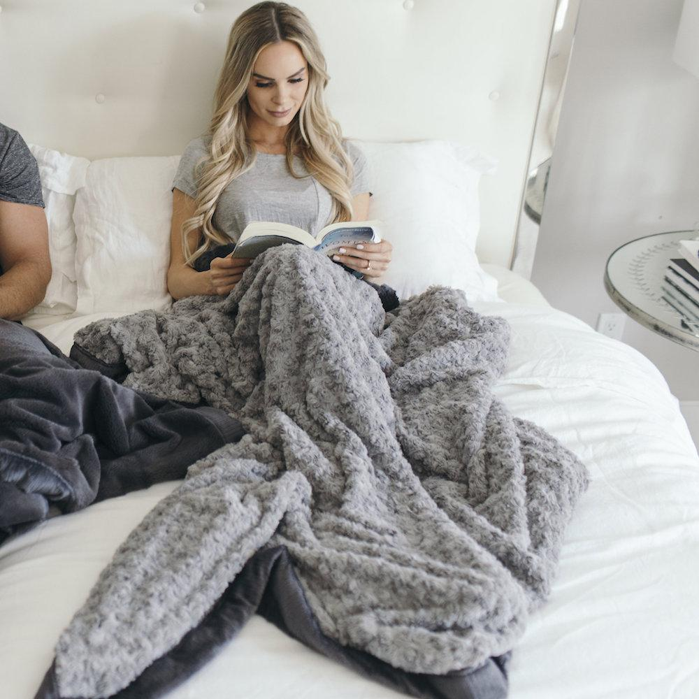 Beautiful woman lounging in bed reading a book while snuggled up in a cozy adult blanket.